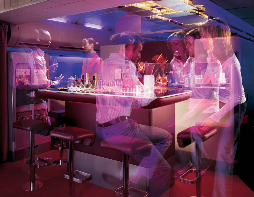 Virtual Reality Scene showing people gathered around a bar area inside a plane