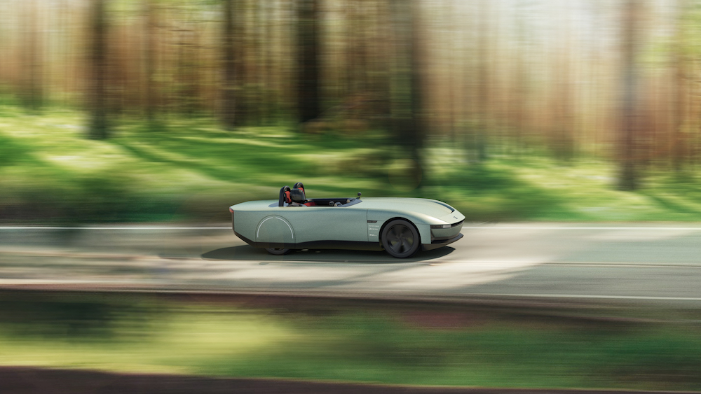 Image shows the design for an all-electric concept car called AURA, the sage-green, two-seater car is shown travelling along a road through a forest.